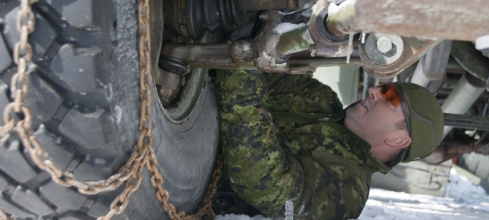 Sgt Louis Pedneault installs traction chains on the wheels of his vehicle during Exercise RAFALE BLANCHE at 5 Canadian Mechanized Brigade Group