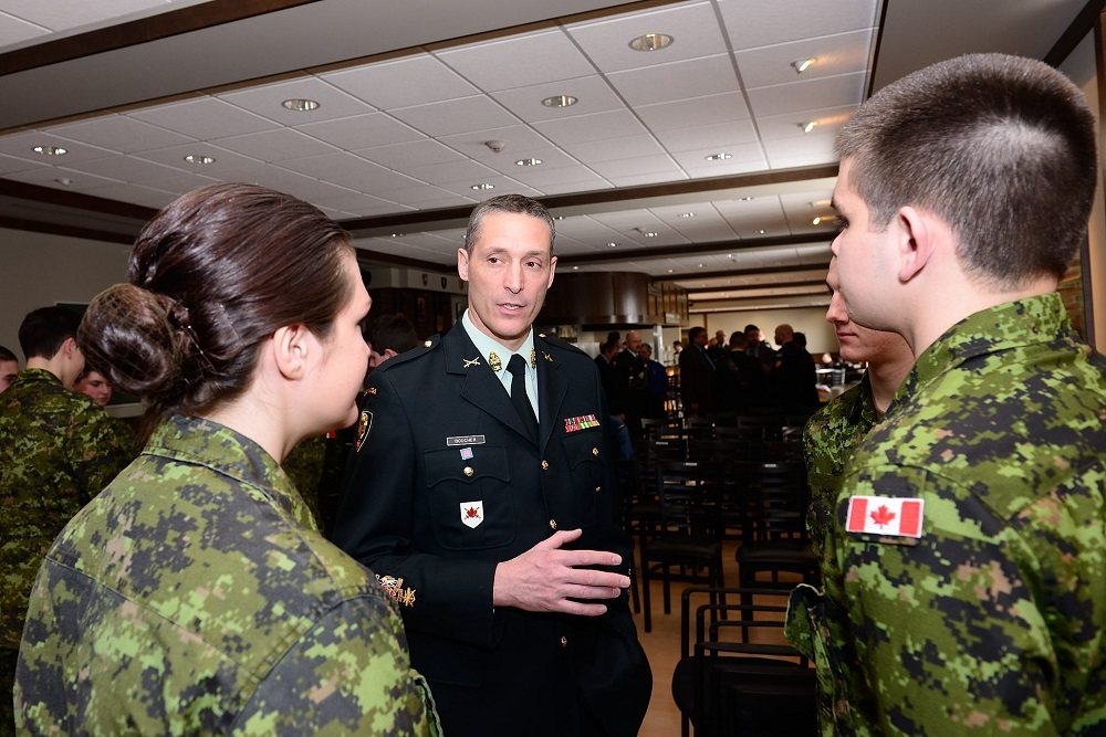 A group of young people in military camouflage uniforms speak with an Army Sergeant Major in uniform in a room full of people.