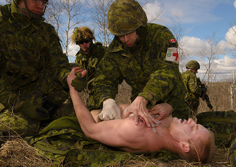 Private Nolan Caribou (left) comforts Private Braedan Peters, while Corporal Jeremiah Sinclair from 17 Field Ambulance treats his wound during a simulated casualty evacuation during Collective Training 6 at CFB Shilo on March 19, 2016.  Photo: Cpl Jean Archambault