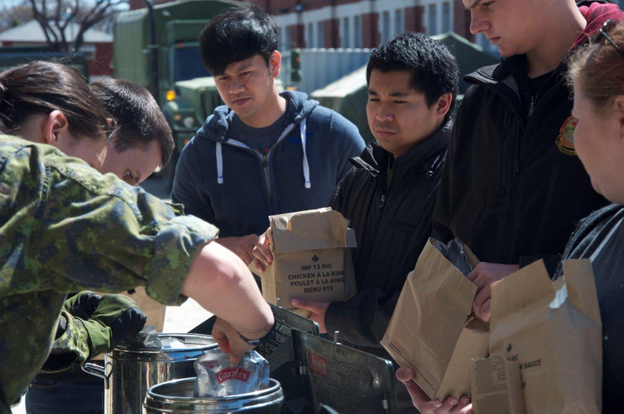 Participants look on curiously as they are served Individual Meal Packages for lunch during 38 Service Battalion's event, Soldier for a Day, held at Minto Armouries in Winnipeg on April 30, 2016.  Photo by 2Lt Stacie Nelles, 38 CBG PAO.