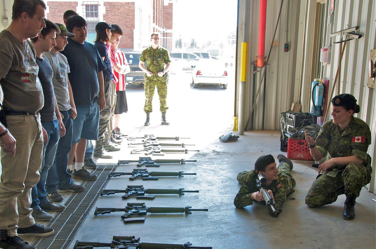 Corporal Chantal Chapil and Corporal Eric Penny explain the prone position during the weapons training portion of Soldier for a Day, hosted by 38 Service Battalion at Minto Armouries on April 30, 2016.  Photo by 2Lt Stacie Nelles, 38 CBG PAO.
