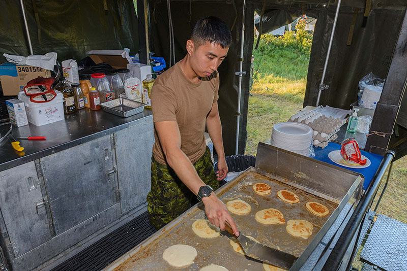 Corporal Sang Chin prepares breakfast in the field for members of 38 Service Battalion during Exercise BISON WARRIOR held at CFD Dundurn, Sask., from August 13–21, 2016 Photo; Cpl Jean Archambault