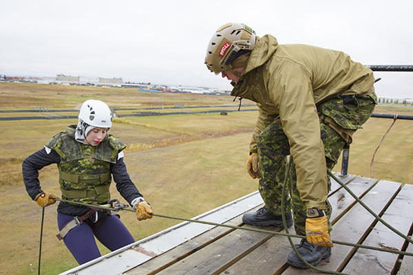Sergeant Jason Debourke (right) with Third Battalion, Princess Patricia's Canadian Light Infantry (3 PPCLI) helps an athlete from the University of Alberta Pandas Women's Hockey Team descend from the rappel tower during the 3 PPCLI Soldier for a Day activity on Oct. 1. Photo: Grant Cree