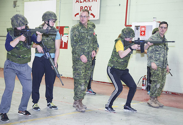 Master Corporal (MCpl) Christopher Wagner and MCpl Bradley Stubert of Third Battalion, Princess Patricia's Canadian Light Infantry (3 PPCLI) supervise athletes from the University of Alberta Pandas Women's Hockey Team as they shoot C-7 service rifles in the Urban Operations Centre during the 3 PPCLI Soldier for a Day activity.  Photo: Grant Cree