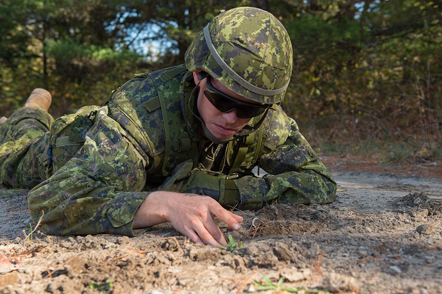 A Canadian Armed Forces member inspects the road for simulated improvised explosive devices during Exercise ARDENT DEFENDER 2017 in Borden, Ontario on October 17, 2017.