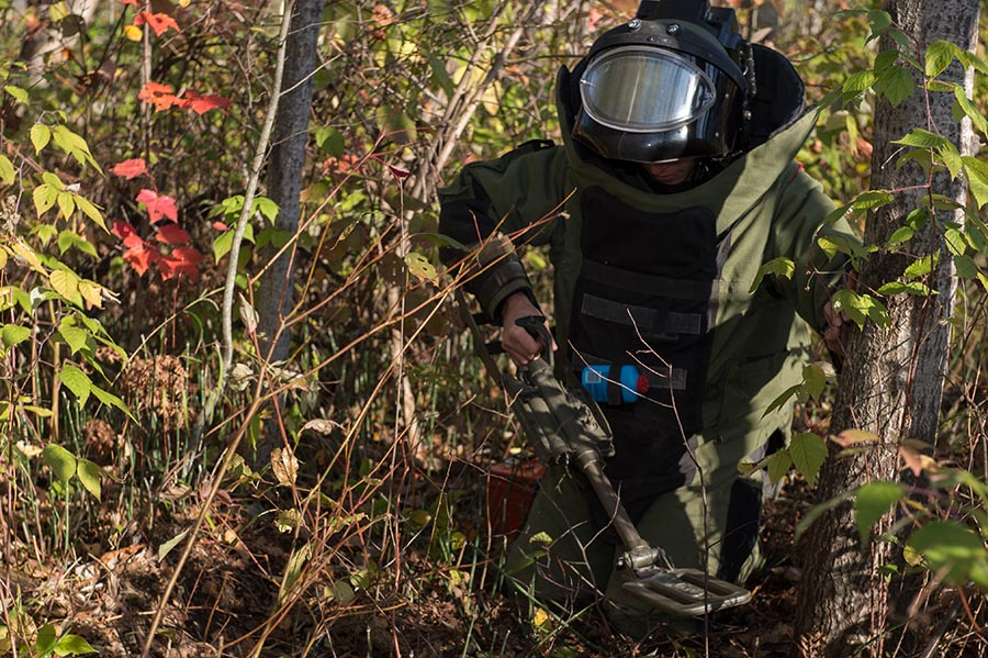 An Explosive Ordnance Disposal Technician inspects the ground with a metal detector for simulated improvised explosive devices as part of Exercise ARDENT DEFENDER 2017 in Borden, Ontario on October 18, 2017.