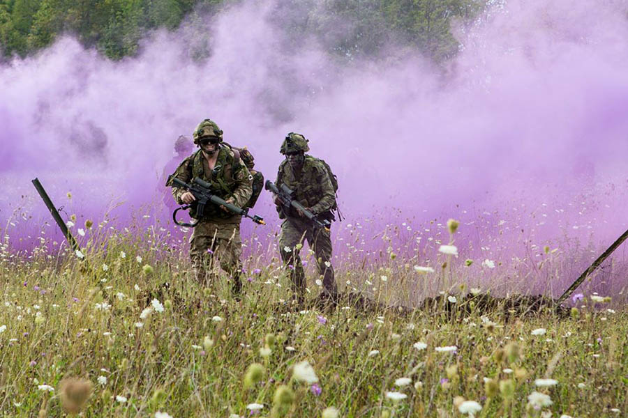 Side by side, British and Canadian soldiers cross freshly blown-up earth as they pass through what just was a razor wire fence as part of a simulated infantry assault during Exercise STEADFAST WARRIOR 2017, held from August 25 to 31 at the 4th Canadian Division Training Centre Meaford in Ontario.